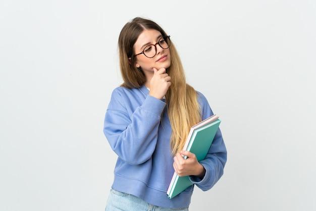 Donna giovane studentessa bionda su bianco che ha dubbi durante la ricerca