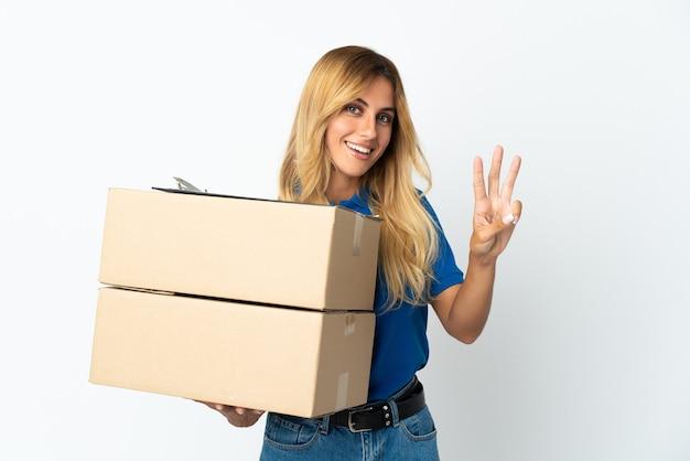 Giovane donna bionda di consegna uruguaiana isolata sul muro bianco felice e contando tre con le dita