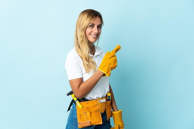Giovane donna bionda elettricista uruguaiano su blu che punta al lato per presentare un prodotto