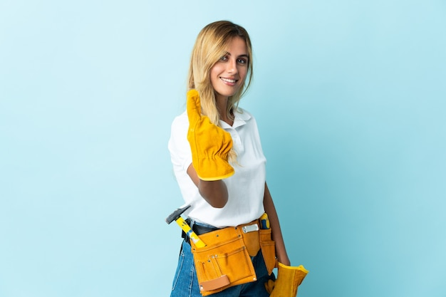 Giovane donna bionda dell'elettricista uruguaiano isolata sulla parete blu che fa gesto venente