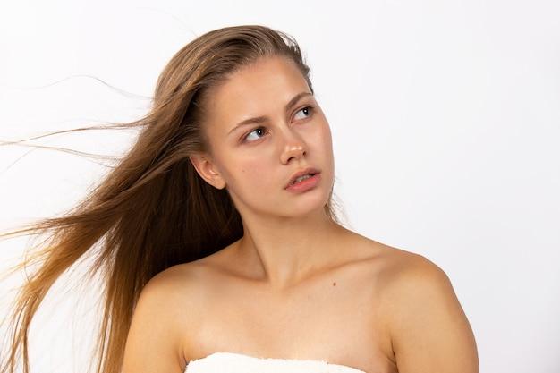 Una giovane bionda con lunghi capelli sani che guarda pensieroso di lato. con una pelle pulita, morbida e sana. capelli sani e concetto di pelle pulita. foto di alta qualità