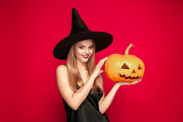 Giovane donna bionda in cappello nero e costume su sfondo rosso. modello femminile caucasico attraente. halloween, venerdì nero, cyber lunedì, saldi, concetto autunnale. copyspace. tiene la zucca, sorride.