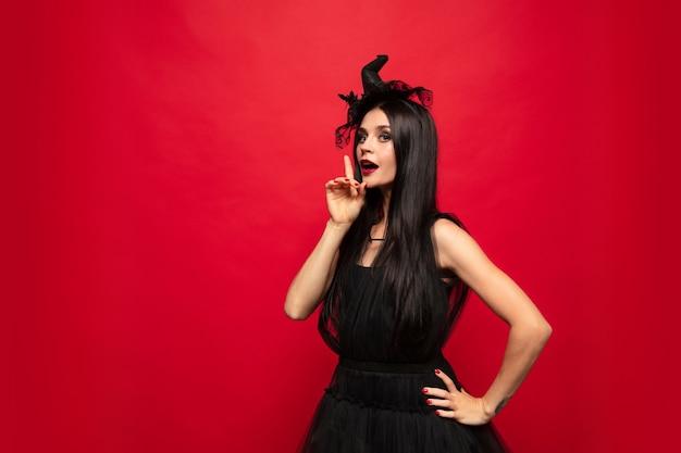 Giovane donna bionda con cappello nero e costume su sfondo rosso