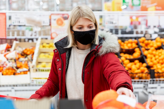 Giovane donna bionda in una mascherina medica nera e in una giacca rossa in un supermercato