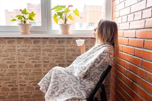 Una giovane donna bionda in una coperta con una tazza bianca di caffè o tè è seduta sul balcone