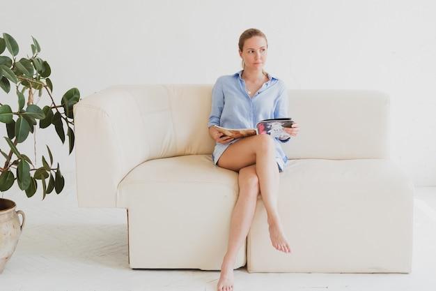 La giovane donna bionda con una camicia blu si siede su un divano in una stanza luminosa e legge una rivista