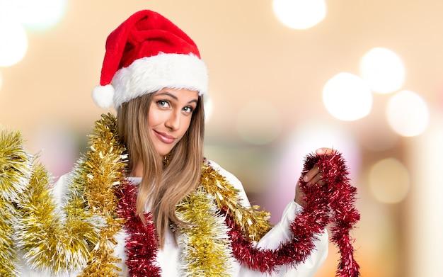 Giovane donna bionda nelle feste di natale sulla parete unfocused