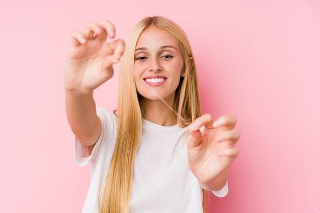 Giovane donna bionda che pulisce i suoi denti con un filo interdentale