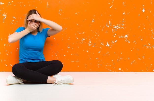 Giovane donna bionda che copre il viso con entrambe le mani dicendo no alla telecamera! rifiutare le foto o vietare le foto seduti sul pavimento