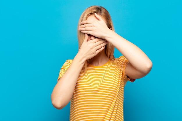 Giovane donna bionda che copre il viso con entrambe le mani dicendo no! rifiutare le foto o vietare le foto