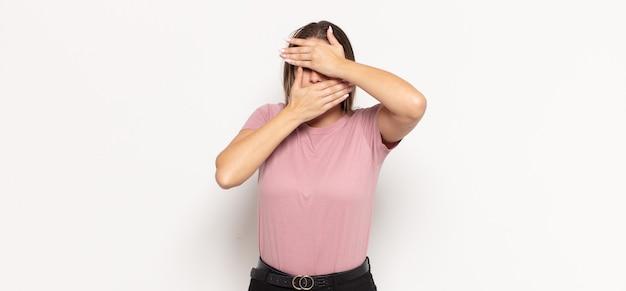 Giovane donna bionda che copre il viso con entrambe le mani dicendo no! rifiutare le immagini o vietare le foto