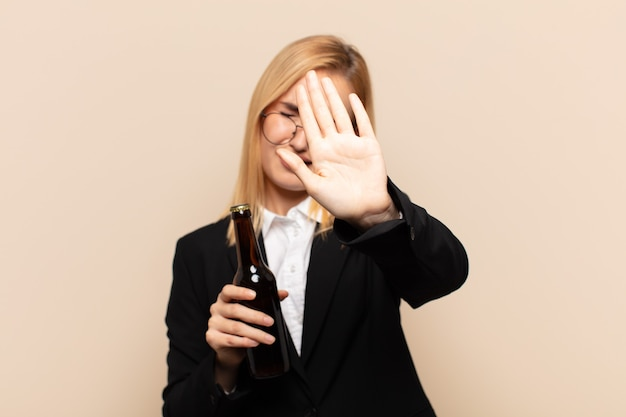 Giovane donna bionda che copre il viso con la mano e mette l'altra mano davanti per fermare la fotocamera, rifiutando foto o immagini
