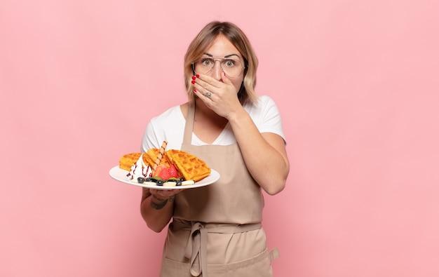 Giovane donna bionda che copre la bocca con le mani con un'espressione scioccata e sorpresa, mantenendo un segreto o dicendo oops