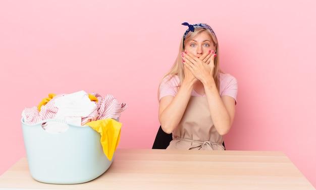 Giovane donna bionda che copre la bocca con le mani con uno scioccato. lavare i vestiti concetto