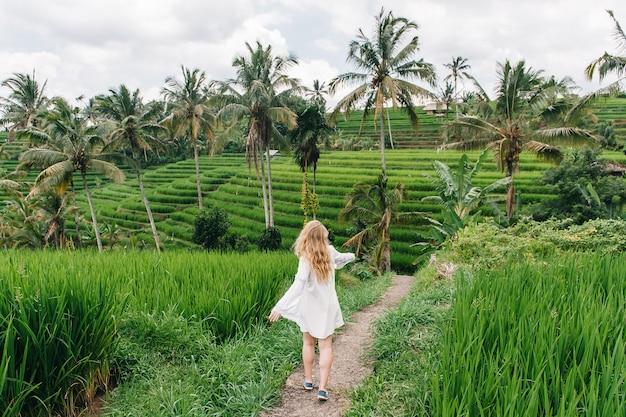 Giovane donna bionda danza sulle risaie dell'isola di bali, indonesia.