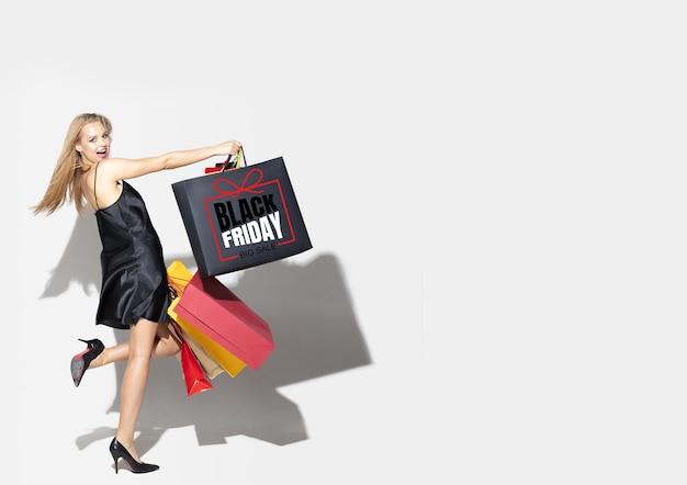 Giovane donna bionda in abito shopping su sfondo nero. modello femminile caucasico attraente. finanza, venerdì nero, cyber lunedì, vendite, concetto autunnale. copyspace. sorridendo, urlando felice.