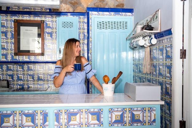Giovane donna bionda vestita con un abito blu che beve una tazza di caffè in una cucina in ceramica blu vintage.
