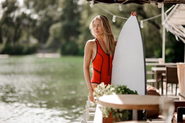 La giovane donna bionda si è vestita in costume da bagno rosso sexy con un wakeboard che sta vicino all'acqua