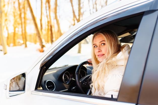 L'autista della giovane donna bionda si siede nella sua macchina bianca e sorride felice. assicurazione, sicurezza, noleggio auto.