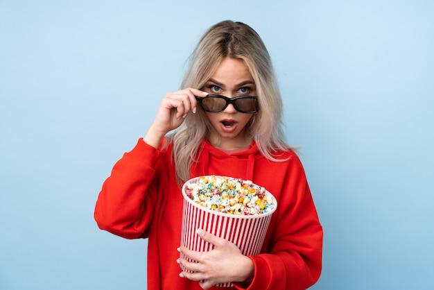 Giovane donna bionda che mangia popcorn