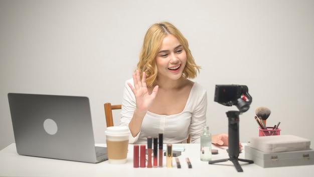Una giovane donna bionda imprenditrice che lavora con il laptop presenta prodotti cosmetici durante lo streaming live online su sfondo bianco studio, vendita online e concetto di blogger di bellezza