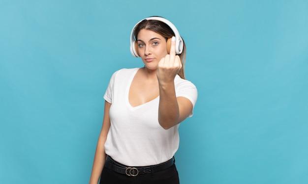 Giovane donna bionda che si sente arrabbiata, infastidita, ribelle e aggressiva, lancia il dito medio, reagisce