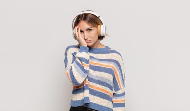 Giovane donna bionda che si sente annoiata, frustrata e assonnata dopo un compito noioso, noioso e noioso, tenendo la faccia con la mano