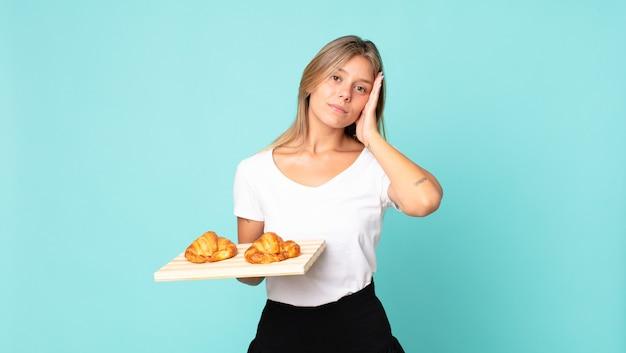 Giovane donna bionda che si sente annoiata, frustrata e assonnata dopo una noiosa e con in mano un vassoio di croissant