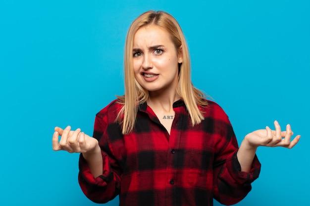 Giovane donna bionda che si sente incapace e confusa, incerta su quale scelta o opzione scegliere, chiedendosi