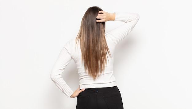 Giovane donna bionda che si sente incapace e confusa, pensando a una soluzione, con una mano sull'anca e l'altra sulla testa, vista posteriore