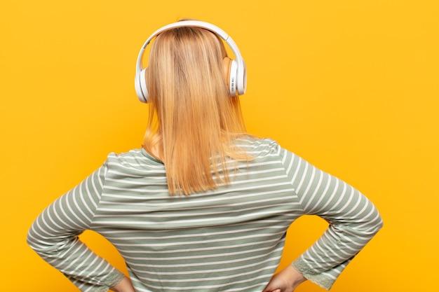 Giovane donna bionda che si sente confusa o piena o dubbi e domande, chiedendosi, con le mani sui fianchi, vista posteriore