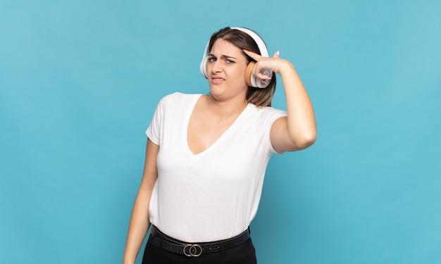 Giovane donna bionda che si sente confusa e perplessa, dimostrando che sei pazzo, pazzo o fuori di testa Foto Premium