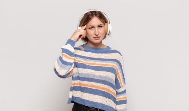 Giovane donna bionda che si sente confusa e perplessa, dimostrando che sei pazzo, pazzo o fuori di testa
