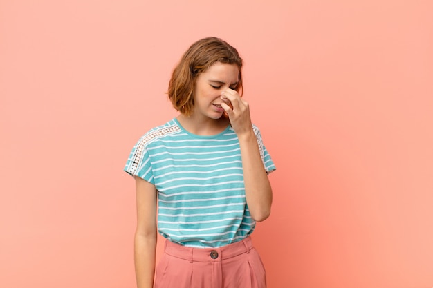 Giovane donna bionda che si sente disgustata, tenendo il naso per evitare di annusare un fetore sgradevole e sgradevole contro la parete di colore piatto