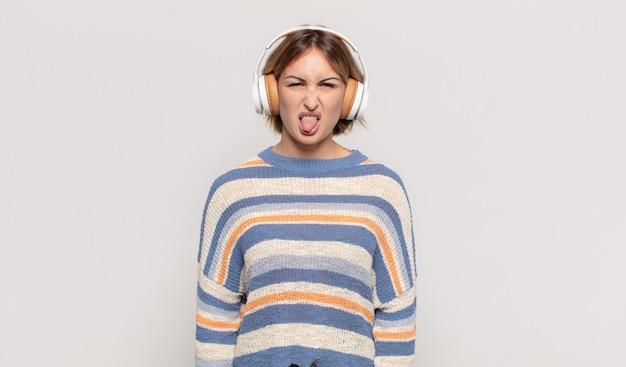 Giovane donna bionda che si sente disgustata e irritata, sporge la lingua, non ama qualcosa di brutto e schifoso