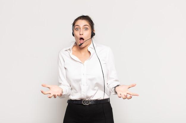 Giovane donna bionda che si sente estremamente scioccata e sorpresa, ansiosa e in preda al panico, con uno sguardo stressato e inorridito