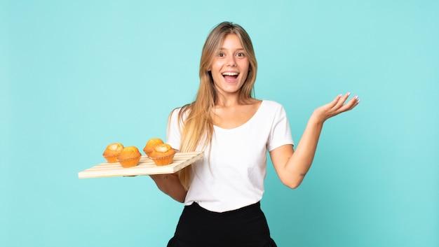 Giovane donna bionda che si sente felice, sorpresa di realizzare una soluzione o un'idea e con in mano un muffin troy