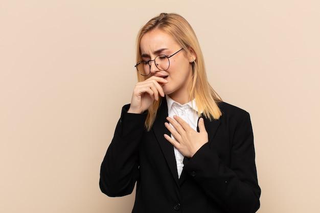 Giovane donna bionda che si sente male con mal di gola e sintomi influenzali, tosse con la bocca coperta