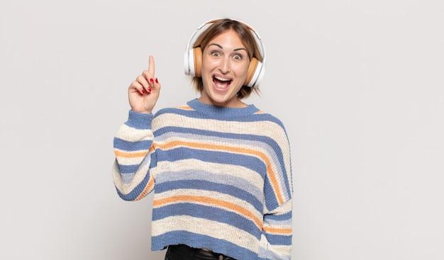 Giovane donna bionda che si sente come un genio felice ed eccitato dopo aver realizzato un'idea, alzando allegramente il dito, eureka!