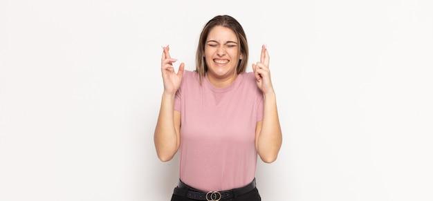 Giovane donna bionda che si sente nervosa e piena di speranza, incrociando le dita