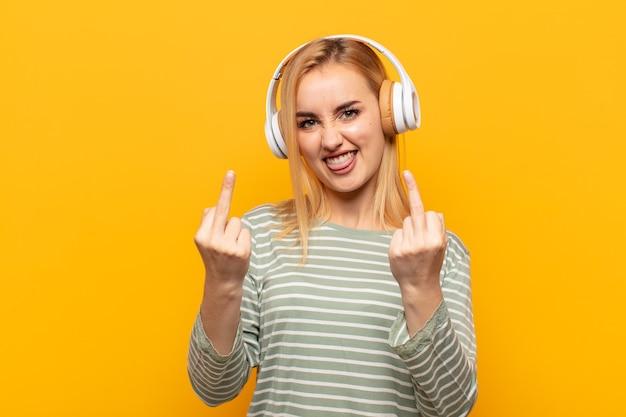 Giovane donna bionda che si sente provocante, aggressiva e oscena, lancia il dito medio, con un atteggiamento ribelle