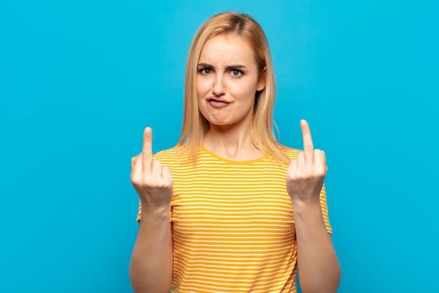 Giovane donna bionda che si sente provocatoria, aggressiva e oscena, lanciando il dito medio, con un atteggiamento ribelle