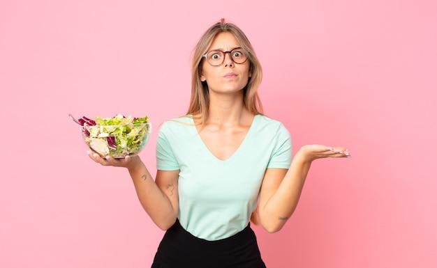Giovane donna bionda che si sente perplessa e confusa e dubita e tiene in mano un'insalata