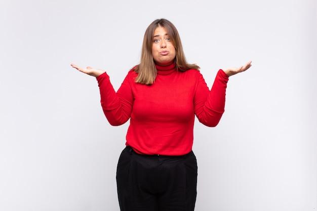 Giovane donna bionda che si sente perplessa e confusa, dubbiosa, ponderata o scegliendo diverse opzioni con un'espressione divertente