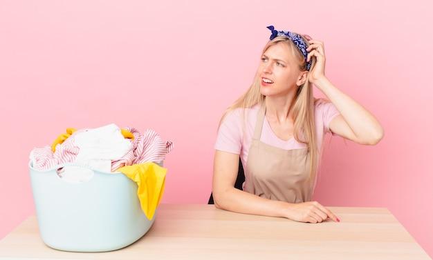 Giovane donna bionda che si sente perplessa e confusa, grattandosi la testa. lavare i vestiti concetto