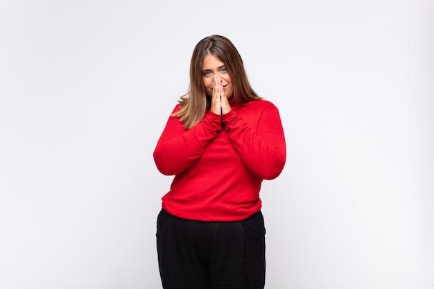 Giovane donna bionda che si sente preoccupata, fiduciosa e religiosa, pregando fedelmente con i palmi premuti, chiedendo perdono