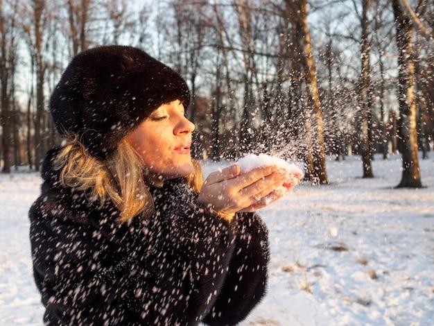 Una giovane donna bionda con una pelliccia e un cappello di pelliccia di visone soffia via neve soffice dai palmi palm