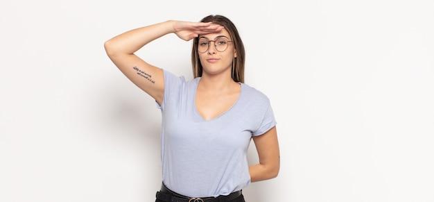 Giovane donna bionda che saluta la telecamera con un saluto militare in un atto di onore e patriottismo, mostrando rispetto