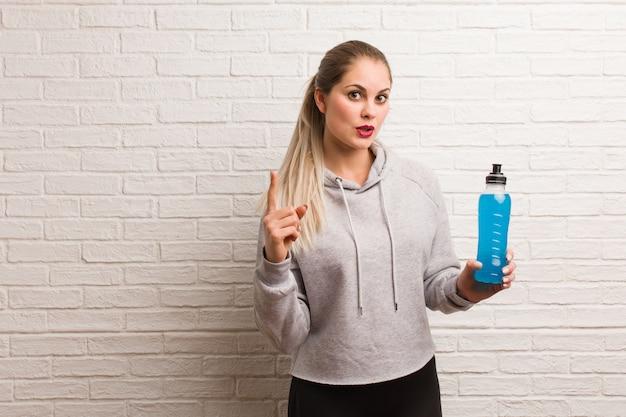 Giovane donna bionda in palestra in possesso di una bottiglia di bevanda isotonica