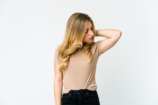 Giovane donna bionda che ha un dolore al collo a causa dello stress, massaggiandolo e toccandolo con la mano